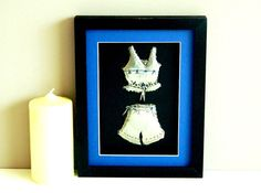 A metal art sculpture pewter embossed pjs trimmed with Capri Blue Swarovski crystals. A black frame and royal blue mount complete this framed metal sculpture.    Build a collage to make a lovely bedroom wall feature.