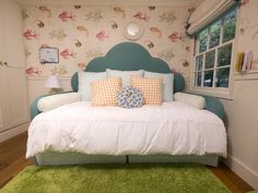 This whimsical child's room features an upholstered, custom-designed daybed with a pullout trundle bed for sleepovers. The headboard's curvy design represents bubbles while the pillows pick up colors from the fish patterned wallpaper.