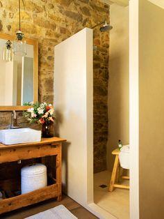 Baño rústico con pared de piedra y ducha de obra 00391517