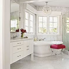 Modern Glam Master Bath with  Pearlescent Finishes  In the mater bath, a vintage Murano glass light fixture and a Lucite footstool add radiance to the serene space.  White floor tiles and silver-gray marble walls reflect sunlight around the room,