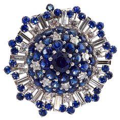 OSCAR HEYMAN Diamond & Sapphire Circular Brooch. Brilliant diamond and sapphire brooch with round brilliant and straight baguette cut diamonds. 20th Century