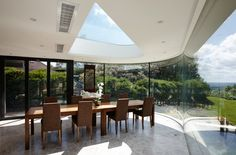 A Dining Room Extension incorporating curved glass, a shaped rooflight and a zinc roof. The concept of a samurai warrior's mask and was influenced by the client's interest in Japan. Also nicknamed Darth Vader due to the dark external materials.