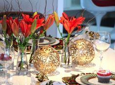 mesa de natal com decoração em vermelho e dourado. Bolas de flores douradas para centro de mesa e arranjos com lírios vermelhos.