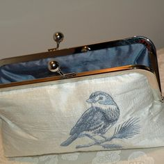 On this beautiful and elegant, softly shaped clutch I have embroidered a blue bird on a branch in a gorgeous brown...Good Enough To eat!...an ivory, knubby silk dupioni fabric....This Dupioni has lots of texture....Featured is a chunky antique gold kisslock frame....The purse is lined with a beautiful brown silk dupioni..... It is interlined with thick batting and interfaced with sturdy, soft interfacing to feel soft and plush in your hand. Triple stitching is used thruout. I can also…