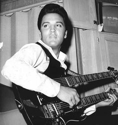 Elvis Presley with a Gibson SG double neck, 6 string bass and 6 string guitar.