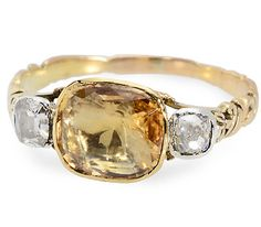 English ring, circa 1750 - 1780, with centered natural golden topaz set east west and flanked with two old mine cut diamonds, 10K yellow gold.