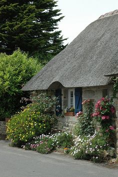 French cottage. The thatched roof and the blue shutters set against the gray stone are so pretty.