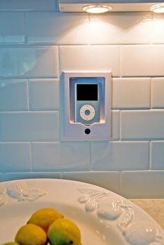 iPod/iPhone dock built into wall and hooked up to speakers throughout the house. Now that's clever! And I would love it.