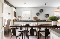In James Huniford's own country kitchen, aged wood accents and steel add layers of texture to simple white cabinets outfitted with humble hardware.
