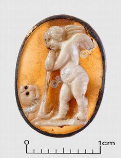 """camée, """"Génie funèbre"""" (camée.60), BnF. Sardonyx, époque romaine.  Le génie est nu, debout et de profil, avec de petites ailes aux épaules. Des deux mains il s'appuie sur le manche de sa houe, et il contemple mélancoliquement une tête de mort qu'il vient d'exhumer."""