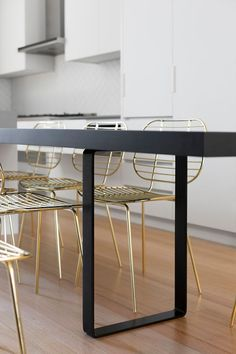Surrounding this modern black kitchen table is a set of gold chairs adds a touch of glam to the space and makes it feel more sophisticated.