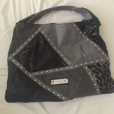 Nicole Lee black and grey purse Nicole lee one strap black and grey purse. There are a few rhinestones missing from the front tag other than that it's in really good condition. In the third picture I turned the purse inside out to show the pattern. There are a few pen marks inside of the purse. Nicole Lee Bags