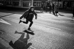 A young teenager riding a skate on the road in front of Zurich main station.