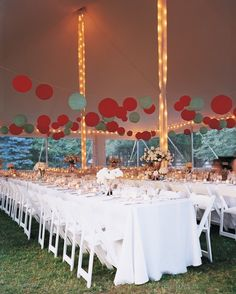 Paper lanterns in the wedding's colors hovered over long banquet tables at this outdoor affair in New York. Strings of lights climbing the tent poles and circling its border brightened the space as evening fell.