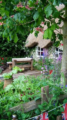 A true English cottage garden complete with thatched roof, old chopping block as a table and a mix of veg in with the flowers and even the old rhubarb forcer as well...love it!