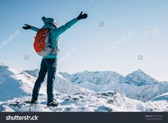 Hiker woman standing with hands up achieving the top, admiring winter mountain landscape. Happy tourist woman in winter. High Tatras, 1987 meter above sea level. Poland, Slovakia