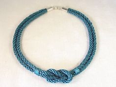 Teal satin kumihimo necklace. Would also work with beaded kumihimo. I like the tie downs on each side of the knot.