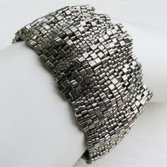 The name of this cuff comes directly from the corrugated metal its texture reminds me of.  Pattern as well as bead size and shape create a fascinating (and sexy) ripple texture that you can see and feel. The different size and shaped beads used in this pattern result in a wonderful undulating, corrugated 3-d surface. The piece can be worn with either the convex or the concave side on the outside, resulting in very different looks.  This beadwoven bracelet is a joy to wear. While it is a…