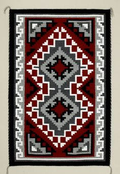 "Ganado Reds, these rugs always have a red background, because Lorenzo Hubbell said so. Here is one of Kathy's renditions of the classic Ganado Red. This is a design which originated in a much simpler pattern invented by Hubbell for use in his printed catalog of ""Indian Blankets."" Hubbell owned the trading post in Ganado in the late 1800s. He made up ""saleable"" designs and had the local Navajos weave them accordingly. The one pattern that has stayed popular is the one you see here by Kathy."