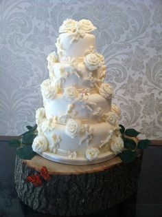 A lovely white chocolate cake covered from head to toe in handmade white chocolate roses and cherubs
