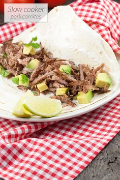 Slow cooker pork carnitas are a Mexican speciality that means 'little meats' and is similar to pulled pork. Served on a tortilla with avocado and lime.
