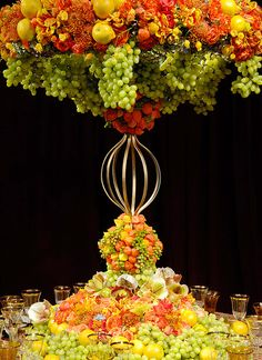 Tall citrus-color centerpiece incorporating fruit.
