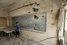 パレスチナ自治区ガザ市(Gaza City)の学校で、爆弾の破片で穴が開いた黒板に字を書く子ども(2014年8月5日撮影)。(c)AFP/MOHAMMED ABED ▼9Aug2014AFP|穴のあいた黒板に字を書く子ども、ガザ http://www.afpbb.com/articles/-/3022725