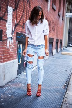 Tash from They All Hate Us looking chic in ripped light denim jeans, relaxed white shirt & lace up heels