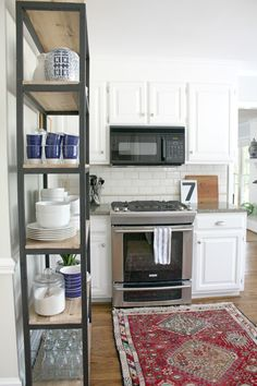 white kitchen with industrial shelving/bookcase for storage
