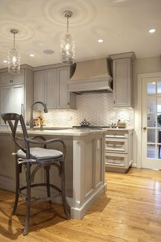 Gray kitchen with gray washed cabinets paired with gray granite countertops and white basketweave tile backsplash.