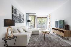 Este salón de un apartamento de Barcelona equilibra perfectamente los muebles modernos de diseño de los '70 con ornamentos originales de la época.