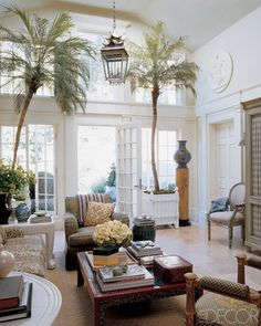 Open and airy tropical sitting room in designer Michael S. Smith's own home. Vaulted ceiling, beautiful french doors and windows, great big pagoda lantern, and the potted palms are just divine.