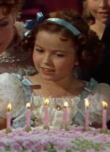 Shirley Temple as a child of 10 or 11 years costumed for The Little Princess, a 1939 Technicolor film. She is seen from the waist up looking at a birthday cake with lit candles placed before her. She has a round face and wide smile. Her hair is arranged in ringlets held in place by a ribbon.