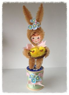 A cute chenille bunny ornament was made using a vintage image and brown chenille stems.. Bunny girl is standing on a decorated vintage spool. She is
