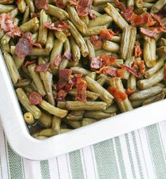 ARKANSAS GREEN BEANS - 5 (15-oz) cans green beans, drained;  12 slices bacon; 2/3 c brown sugar;  1/4 c butter, melted; 7 tsp soy sauce;  1 1/2 tsp garlic powder.  Preheat oven to 350 degrees. Place the drained green beans in a 9×13″ baking pan.