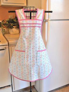 Este delantal estilo vintage se realiza en un diseño de 1940 para un look de moda viejo maravilloso. La tela es una banda de flores azul y rosa y se recorta en rosa sesgo y rick rack.  Se trata de un tamaño mediano.  Máquina de lavado y seca con una plancha caliente.