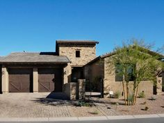 A mix of stucco, stone and wood give this Arizona residence a fusion of Southwest and Tuscan aesthetics. Get the garage door look with  Clopay Canyon Ridge Collection faux wood garage doors, Design 35 in a Walnut stain. www.clopaydoor.com Photo from HGTVRemodels.com