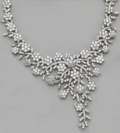 A diamond necklace  of foliate design, the clustering cascade of flowers and vines set throughout with round brilliant-cut diamonds; estimated total diamond weight: 40.00 carats; mounted in eighteen karat white gold; length: 14in.