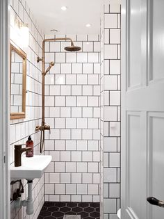 bathroom inspiration: black honeycomb tiles, white subway tiles with dark grout and brass shower fixture