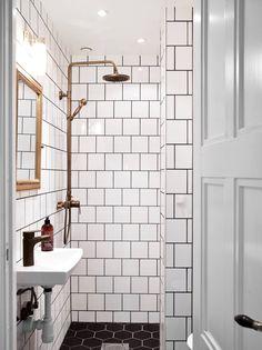 bathroom. white square tiles, black grout, brass details