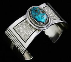 Leonard Nez Rare High Grade Tyrone Turquoise Bracelet #LeonardNez #Cuff This heavy bracelet made by Leonard Nez features a unique setting raised above the shank. The beautiful high grade natural Tyrone turquoise is enclosed in an intricately hand chiseled bezel and overlaid on a platform. The gem is deep blue with vibrant flecks of red host rock matrix. The shank of the piece is hand textured and oxidized in the center. Elegant deep stamped lines and cutouts accent the texturing on either…