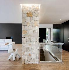 Chiralt Arquitectos I Salón en vivienda moderna con muro de piedra natural y suelo de parquet.