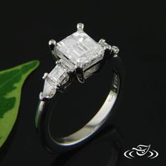Beautiful custom built platinum engagement ring with four prong set center rectangular 1.66ct diamond with 4 prong set side diamonds.