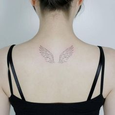 Hand drawn wings tattoo on the upper back.