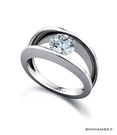 Shimansky Round Brilliant Cut Diamond Millennium Ring. The two bands represent the coming together of two lives joined by a diamond in the middle.  The Millennium design is exclusive to Shimansky.