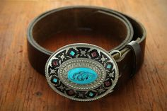 Southwestern design belt buckle with turquoise and red accents surrounded by intricate designs.