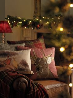 Rich berry hues and an assortment of cushions create that festive, cosy atmosphere. Laura Ashley