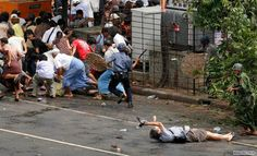 A Japanese videographer is sprawled on the pavement, after being fatally wounded during a street demonstration in Myanmar.  2008
