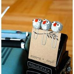 Three little owls sitting on a paperclip