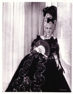 Norma Shearer Marie Antoinette screen-worn dress. (MGM, 1938) Vintage opulent black velvet and lace 2-piece period gown worn by Norma Shearer as the title character in the period epic Marie Antoinette. Trimmed in gathered black and silver bullion lace along neckline, lace tiered sleeves and hem with velvet ribbon details at shoulders. Silver and black ribbon brocade ornamentation cascades down the front of the voluminous skirt with tiered lace at bottom front hem, and severe bustle measuring…